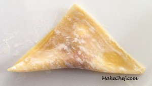 Folding dumpling into triangle.